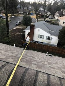 A picture of a person cleaning the roof gutter