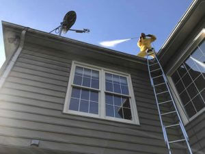 A person doing roof and gutter pressure cleaning